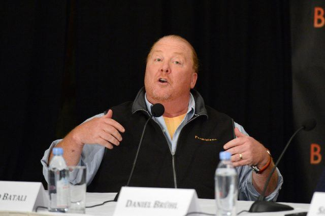 Mario Batali speaking while sitting at a table.