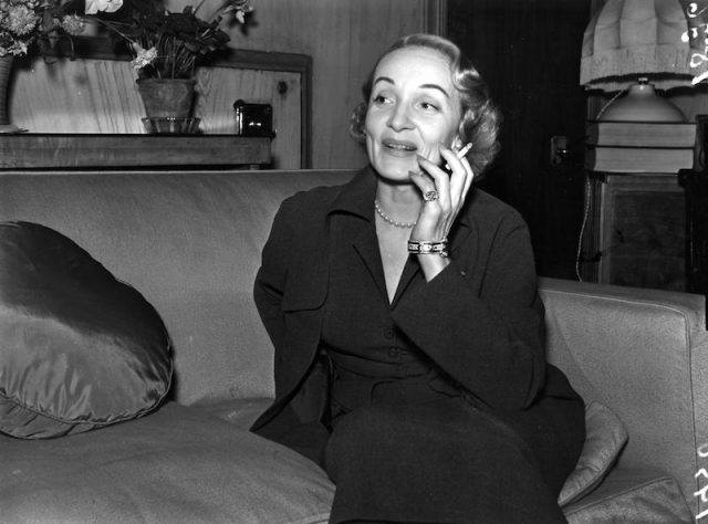 Marlene Dietrich speaking on a cellphone on a couch.