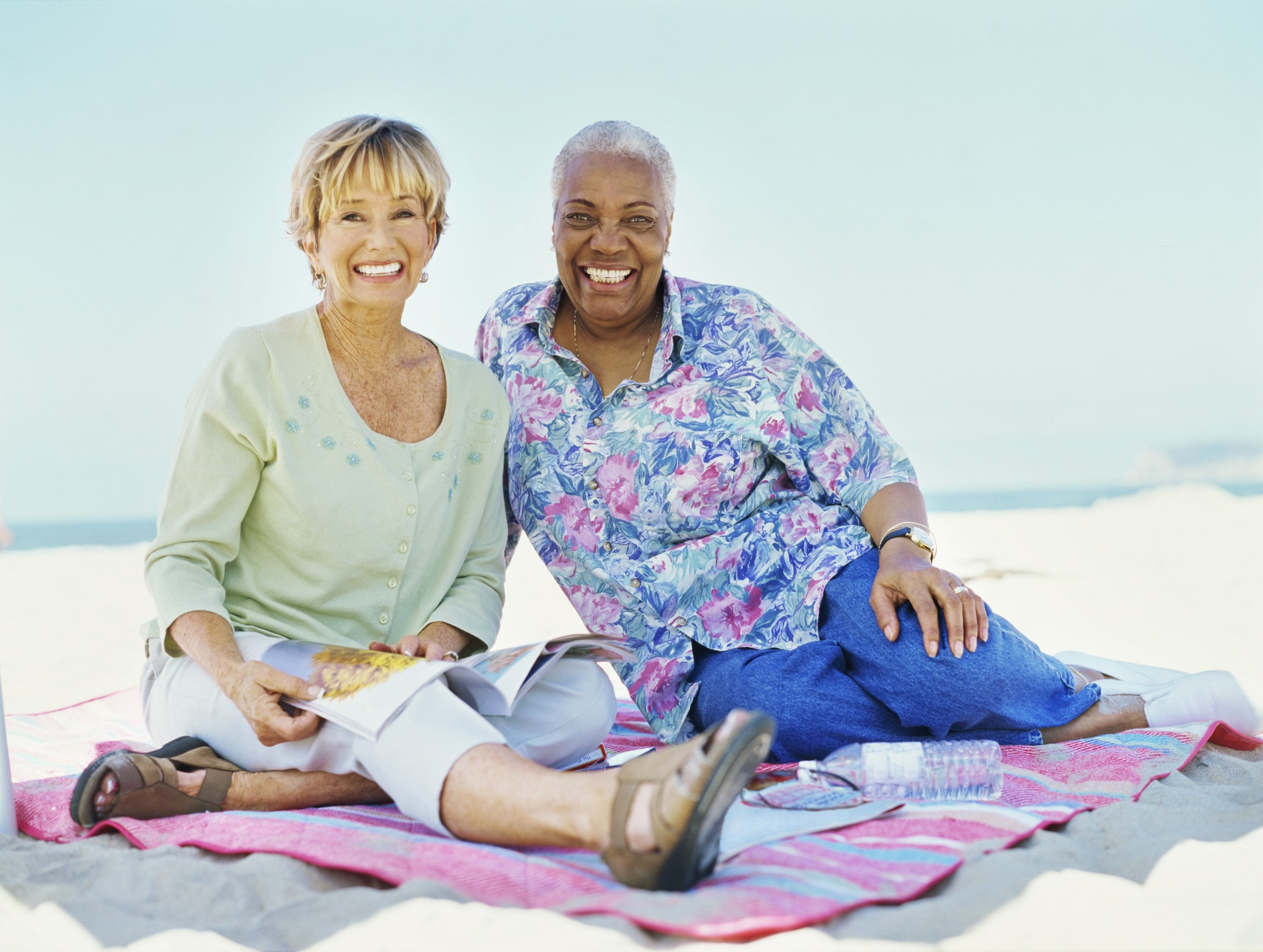 portrait of two mature women sitting on the beach