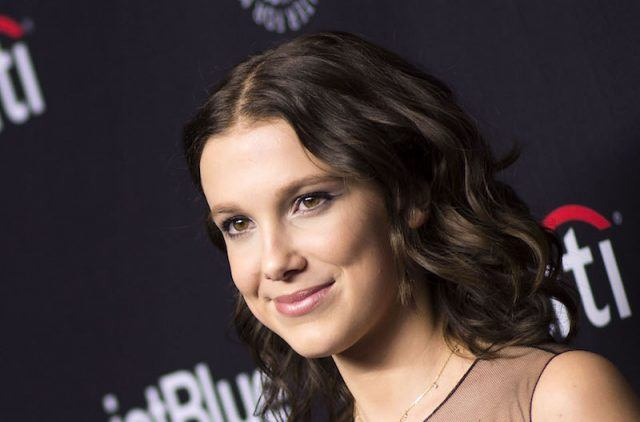 Millie Bobby Brown smiling while on a red carpet.