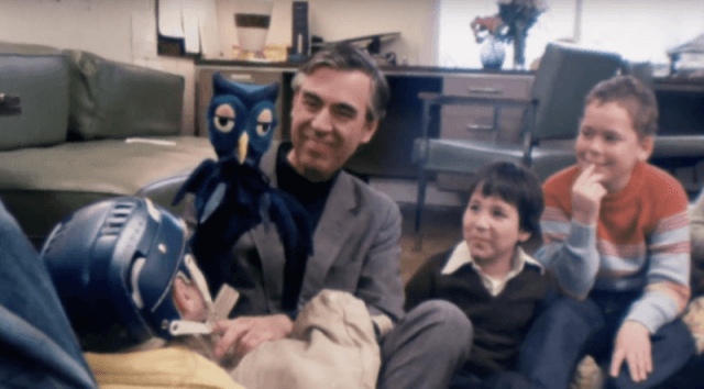 Mister Rogers showing a puppet to children.