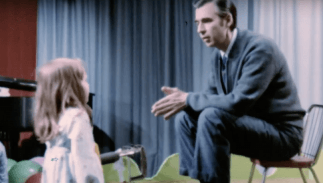 Mister Rogers speaking to a child on set.