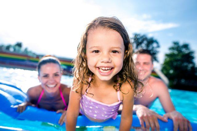 Mother, father and daughter in swimming pool