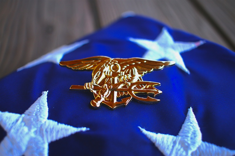 Navy SEAL trident rests atop a folded American flag