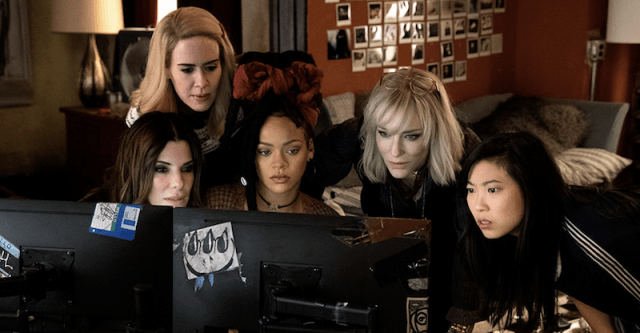 The cast of 'Ocean's 8' gathered around a computer.