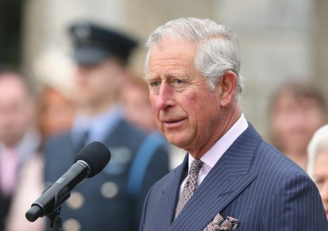 Prince Charles standing in front of a microphone.