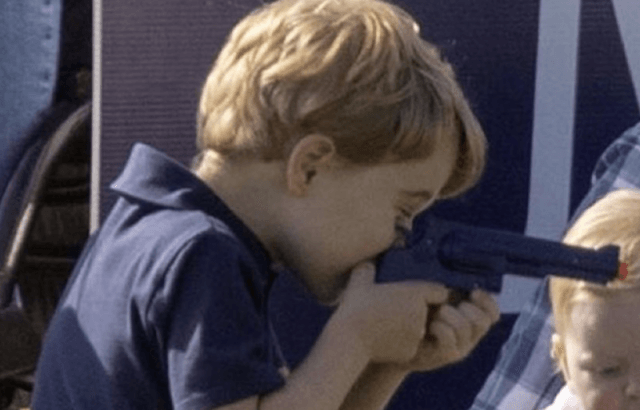 Prince George aiming his toy gun.