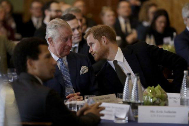 Prince Harry leaning towards Prince Charles.