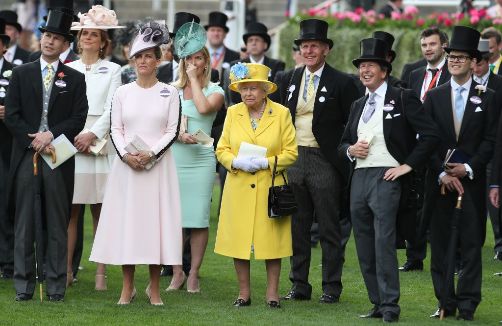 Britain's Queen Elizabeth II (C) stands with her Bloodstock and Racing Advisor, John Warren (3R) as they watch the Wolferton Rated Stakes race on day one of the Royal Ascot horse racin