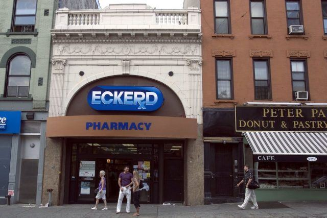 Pedestrians walk by an Eckerd Pharmacy on Manhattan Avenue