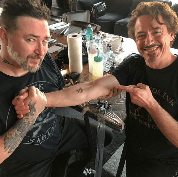 Robert Downey Jr. showing off his Avengers tattoo