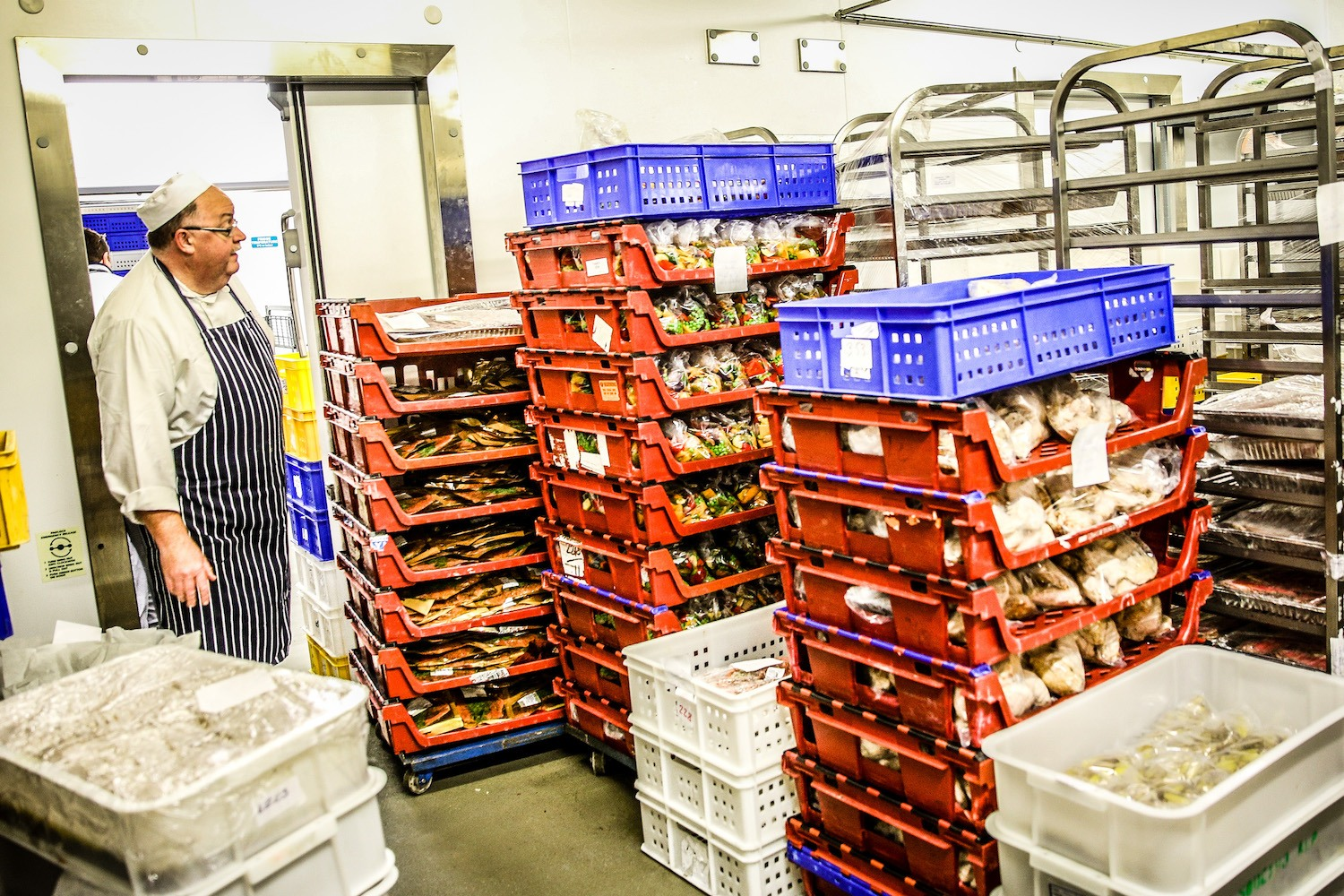 A chef collects ingredients from a cold store in the general kitchen during day four of Royal Ascot
