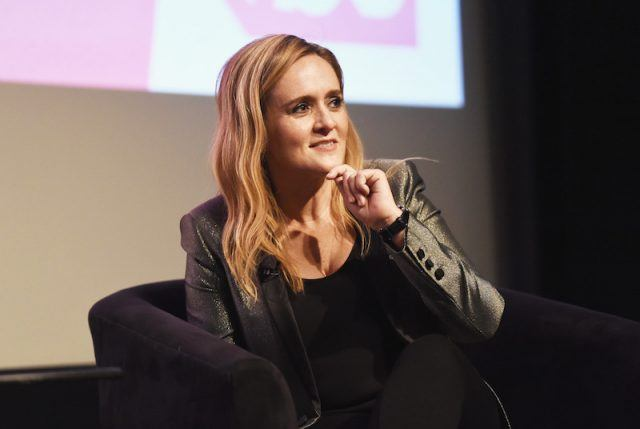 Samantha Bee sits on a black chair on stage.