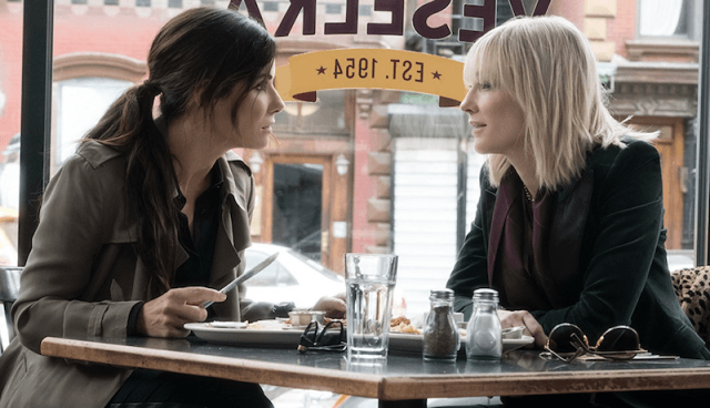 Sandra Bullock and Cate Blanchett sitting in a cafe in 'Ocean's 8'.