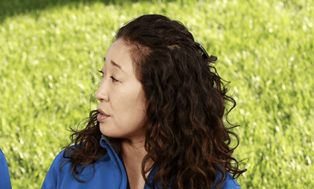 Sandra Oh sitting outside on a bench in 'Grey's Anatomy'.