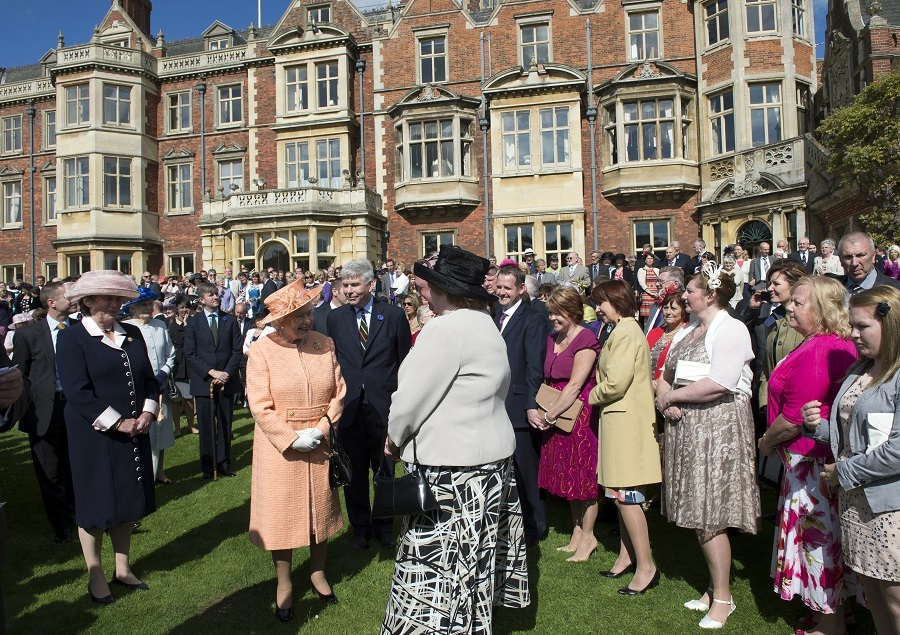 Queen Elizabeth II (C) talks with guests during a garden party in honour of her diamond jubilee at the Queen's Sandringham Estate