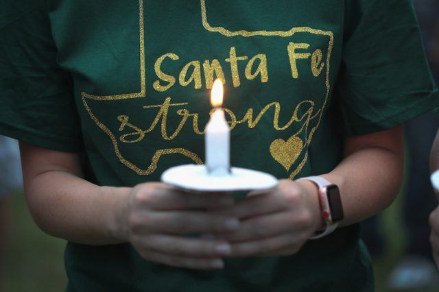 A mourner holds a candle.