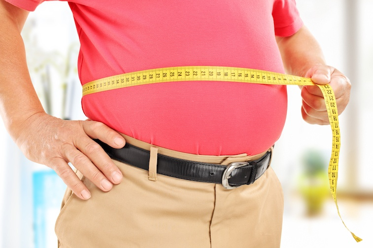 Man measuring his stomach for weight gain