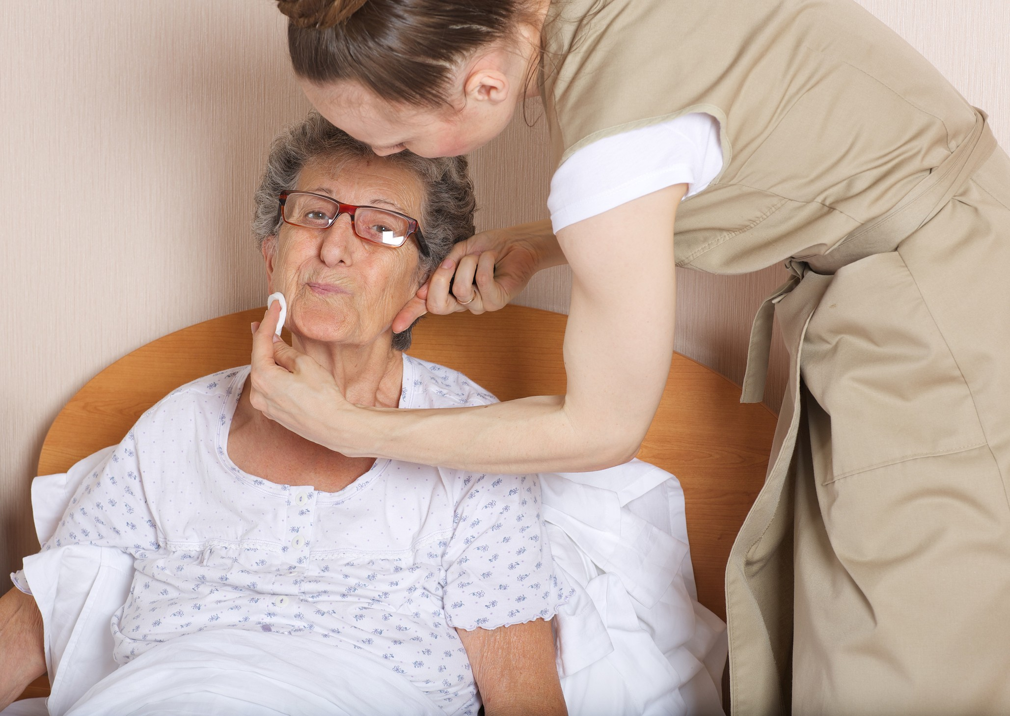 Young social work assistant takes care of a senior woman between 70 and 80 years old.