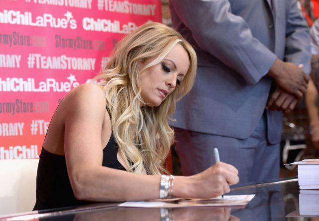Stormy Daniels autographs a photo during a fan meet and greet at Chi Chi LaRue's