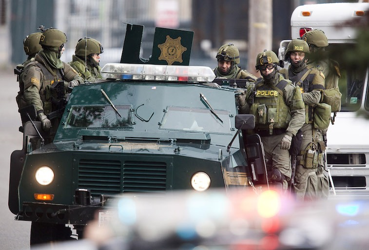 SWAT team members ride on a armored vehicle
