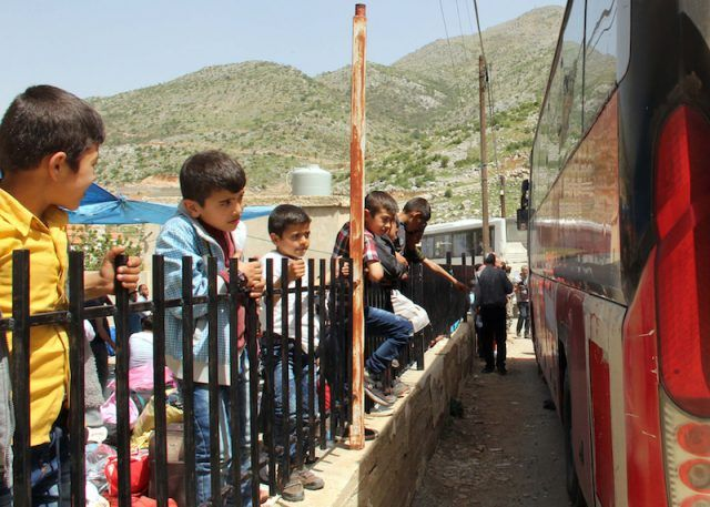 A group of Syrian children waiting to board a bus.