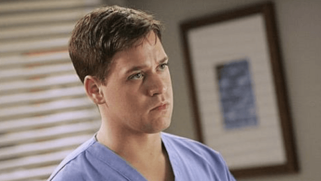T.R. Knight standing in an office in 'Grey's Anatomy'.