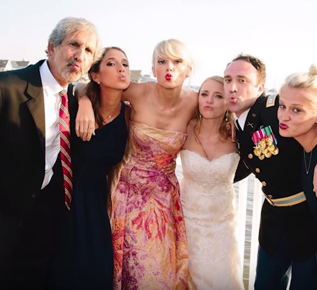 Taylor Swift poses with the bride and groom