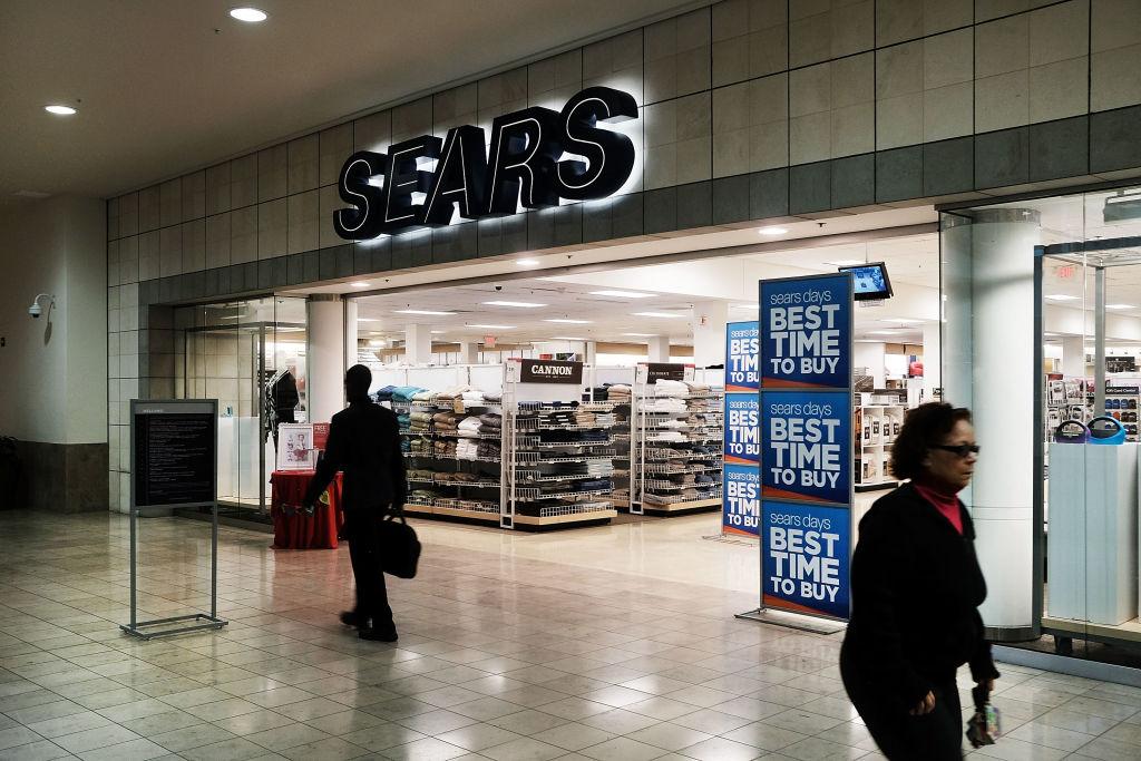 People walk by a Sears store in a nearly empty Westfield Meriden shopping mal