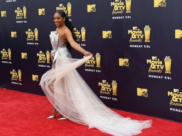 Tiffany Haddish wearing a silver dress on the red carpet.