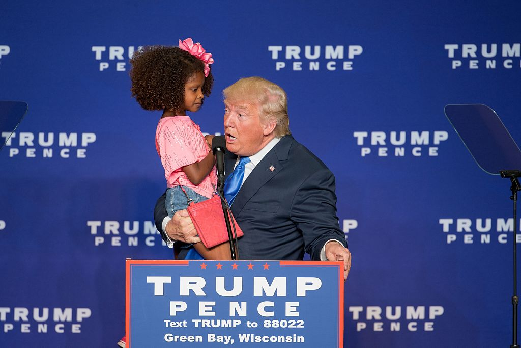 Republican presidential nominee Donald Trump holds a child