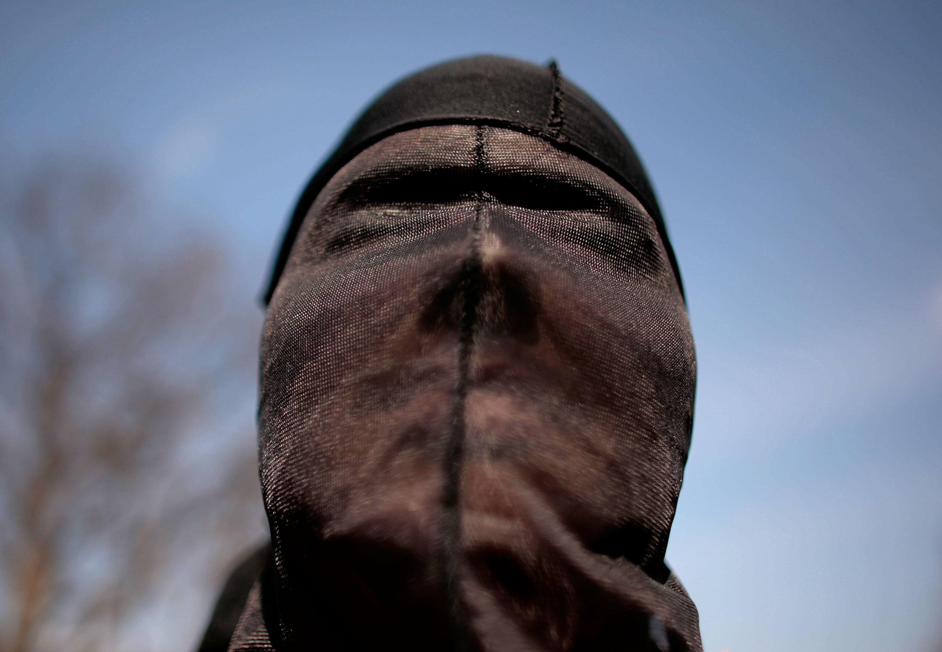 """A demonstrator dresses as a """"detainee"""" during a rally to """"demand Congressional action to stop torture"""""""