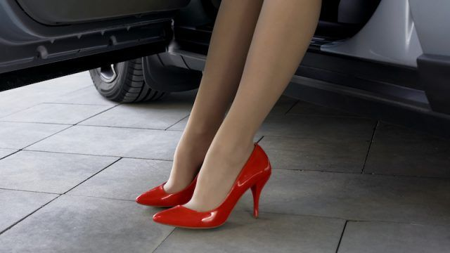 A woman with red high heels emerging from a car.