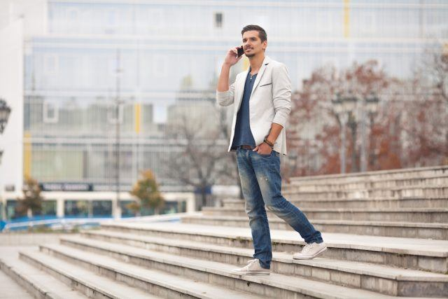 Young man walking down the stairs and talking on the phone