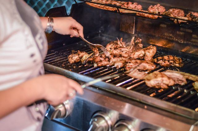 Woman lighting a gas grill
