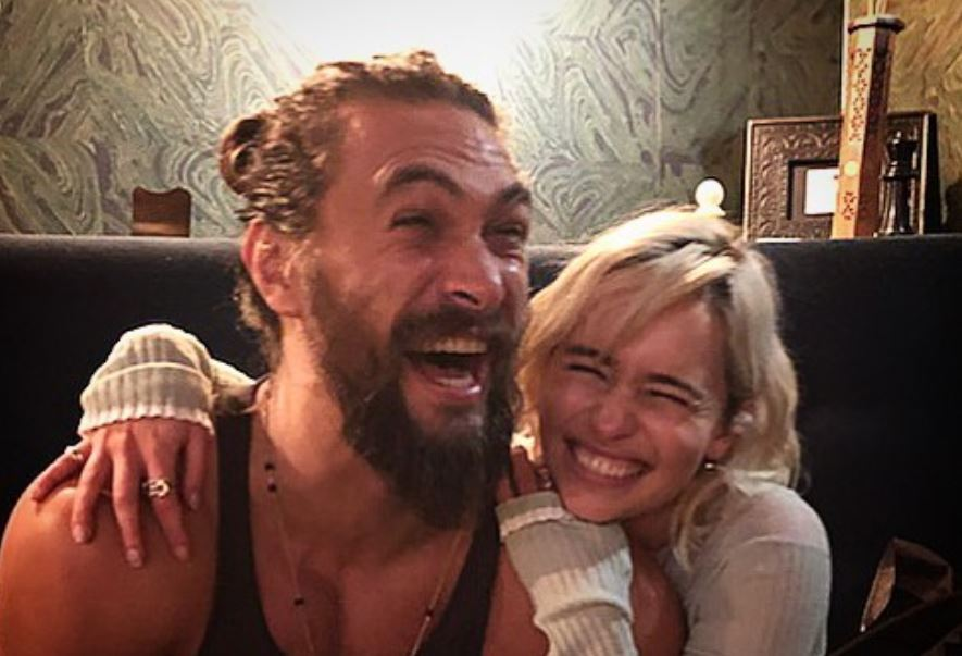 Jason Momoa and Emilia Clarke laughing.