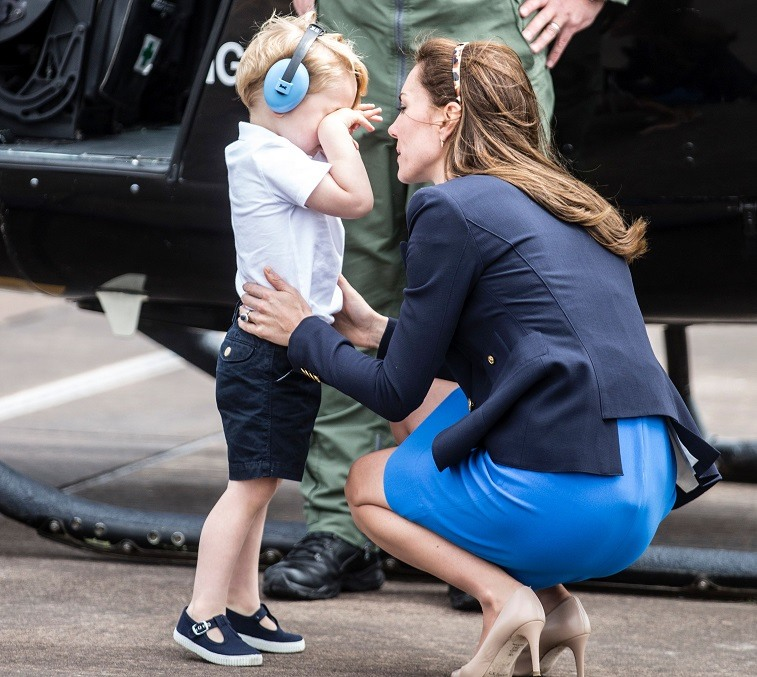 Britain's Prince George rubs his eyes as he speaks with his mother Catherine, Duchess of Cambridge, during a visit to the Royal International Air Tattoo at RAF Fairford in western England, on July 8, 2016.