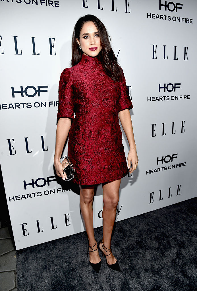 Meghan Markle poses in a red dress.