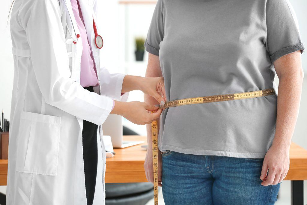 An overweight woman visits a doctor.
