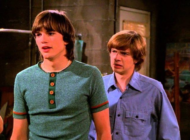 Eric and Kelso standing in the gang's basement.