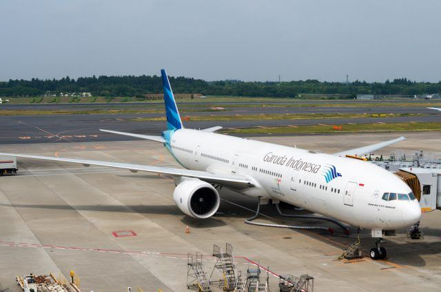 A Garuda Indonesia plane being serviced on the tarmac of Tokyo Narita Airport