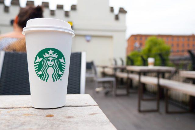 A hot beverage from Starbucks sits on a table