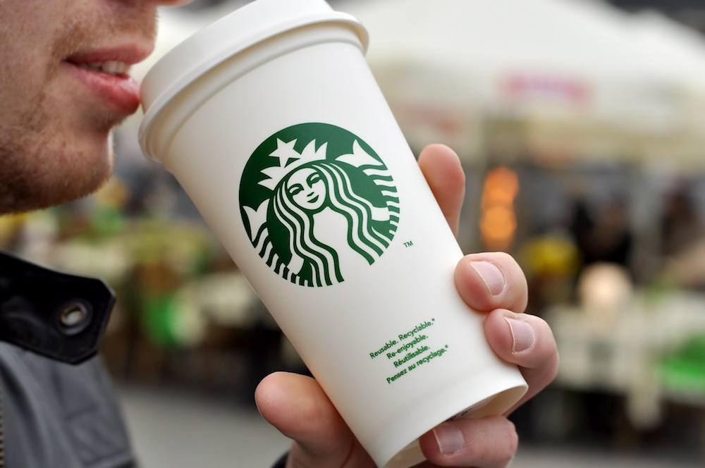 A man holds a hot beverage from Starbucks