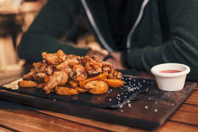 Customer with chicken wings at a restaurant