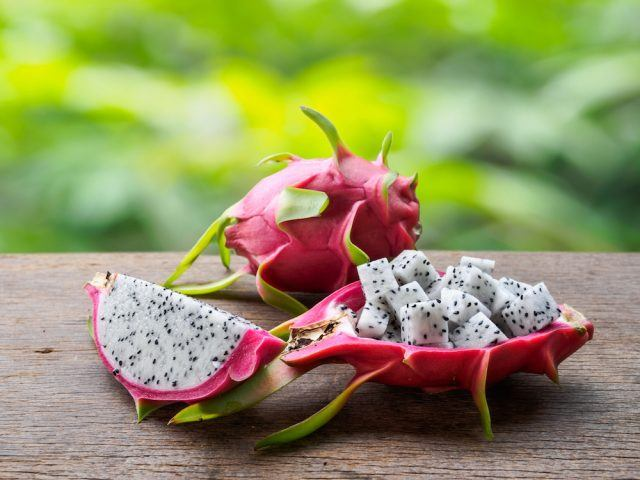 Fresh dragon fruit slice and cubes on wooden table