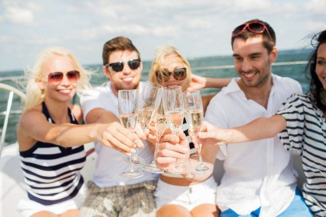 Friends toast glasses of champagne on a yacht