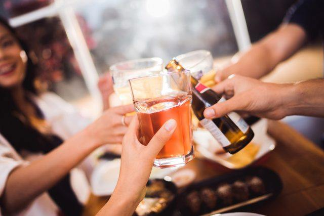 Friends toast with beer at a pub