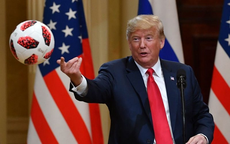 President Donald Trump throws to his wife (unseen) a ball of the 2018 football World Cup that he received from Russia's President as a present during a joint press conference after a meeting at the Presidential Palace in Helsinki, on July 16, 2018.