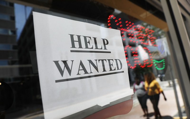 """MIAMI, FL - JUNE 01: A """"help wanted"""" sign hangs on a window of a restaurant on June 1, 2018 in Miami, Florida. The U.S. economy gained a stronger-than-expected 223,000 jobs last month and the unemployment rate edged down to an 18-year low."""