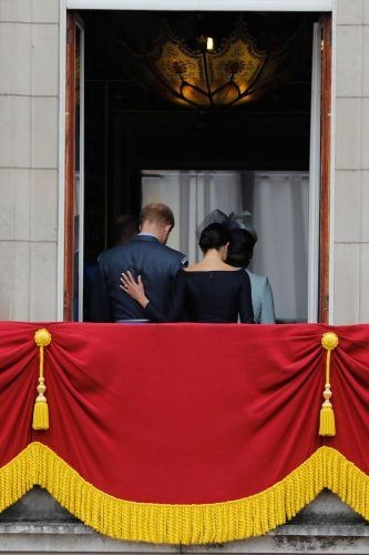 Meghan Markle puts her hand on Prince Harry's back as they leave the balcony of Buckingham Palace